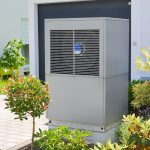 Luftwärmepumpe für Heizung und Warmwasser vor einem Mehrfamilienhaus