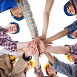 Large group of construction worker stacking hands. Isolated on white